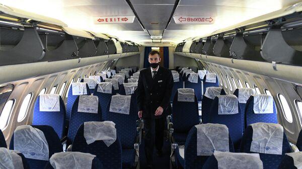 Бортпроводник в салоне самолета Ту-154 авиакомпании Алроса в аэропорту Толмачево в Новосибирске