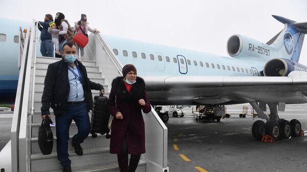 Пассажиры спускаются по трапу из самолета Ту-154 авиакомпании Алроса на перроне в аэропорту Толмачево в Новосибирске