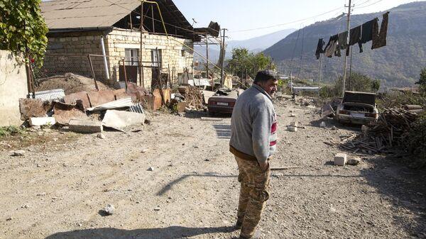 Мужчина возле своего дома, пострадавшего в результате обстрелов Степанакерта