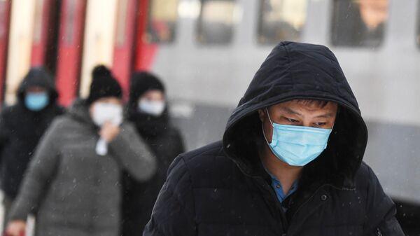 Пассажиры в защитных масках на железнодорожной станции в Новосибирске