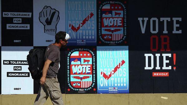 Мужчина проходит мимо предвыборных плакатов в городе Фениксе штата Аризона в США