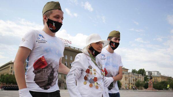 Волонтеры сопровождают ветерана Великой Отечественной войны на военном параде в ознаменование 75-летия Победы в Великой Отечественной войне 1941-1945 годов в Волгограде
