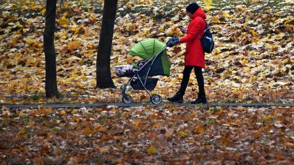 Женщина с детской коляской гуляет в сквере на Ленинском проспекте в Москве