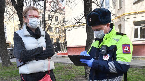 Сотрудник Московской административной дорожной инспекции выписывает штраф за неправильную стоянку автомобиля