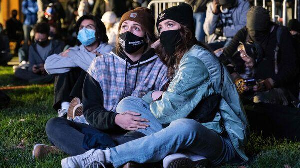 Люди смотрят новости о предварительных результатах президентских выборов 2020 года на площади Макферсон в Вашингтоне