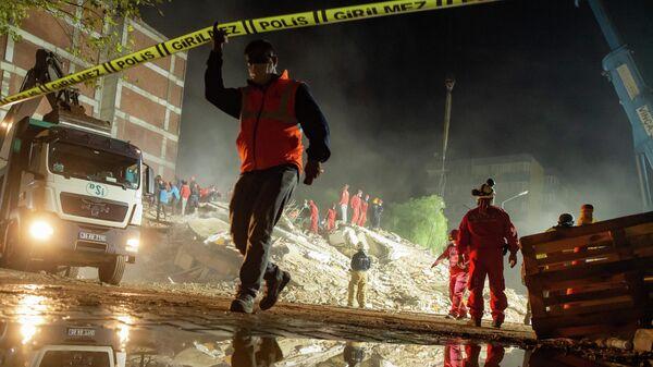 Спасатели ищут выживших среди обломков разрушенного здания в районе Байракли в Измире