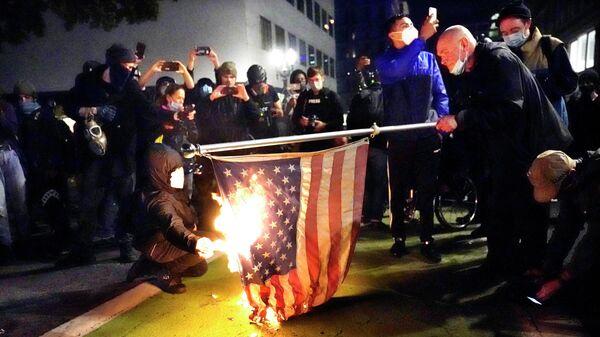 Протестующие в Портленде поджигают американский флаг