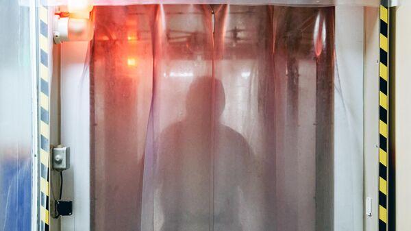Врач проходит санобработку, чтобы выйти из красной зоны госпиталя COVID-19