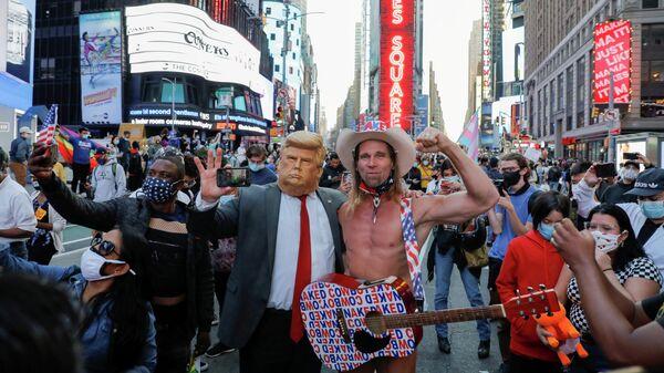 Мужчина в маске с изображением президента США Дональда и Голый ковбой празднуют победу Джо Байдена на выборах президента США в Нью-Йорке
