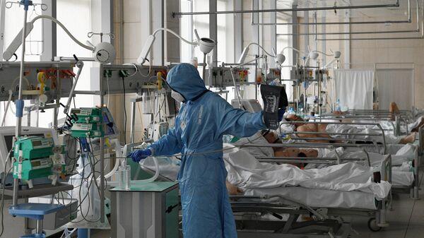 Медицинский работник и пациенты в отделении интенсивной терапии