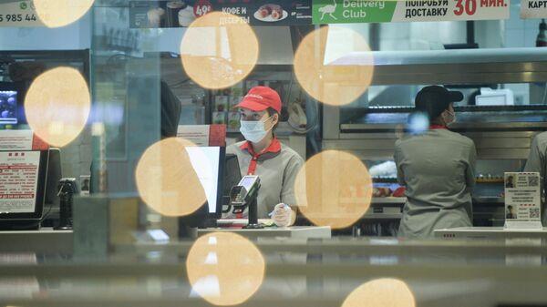 Сотрудница ресторана быстрого питания в защитной маске в Екатеринбурге