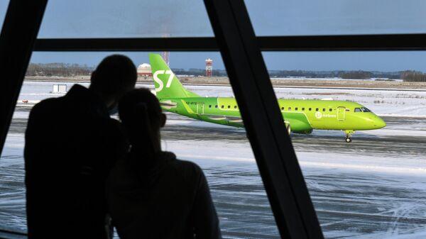 Пассажиры в международном аэропорту Толмачёво в Новосибирске