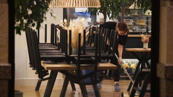Уборщица моет пол в закрытом ресторане на одной из улиц в Москве