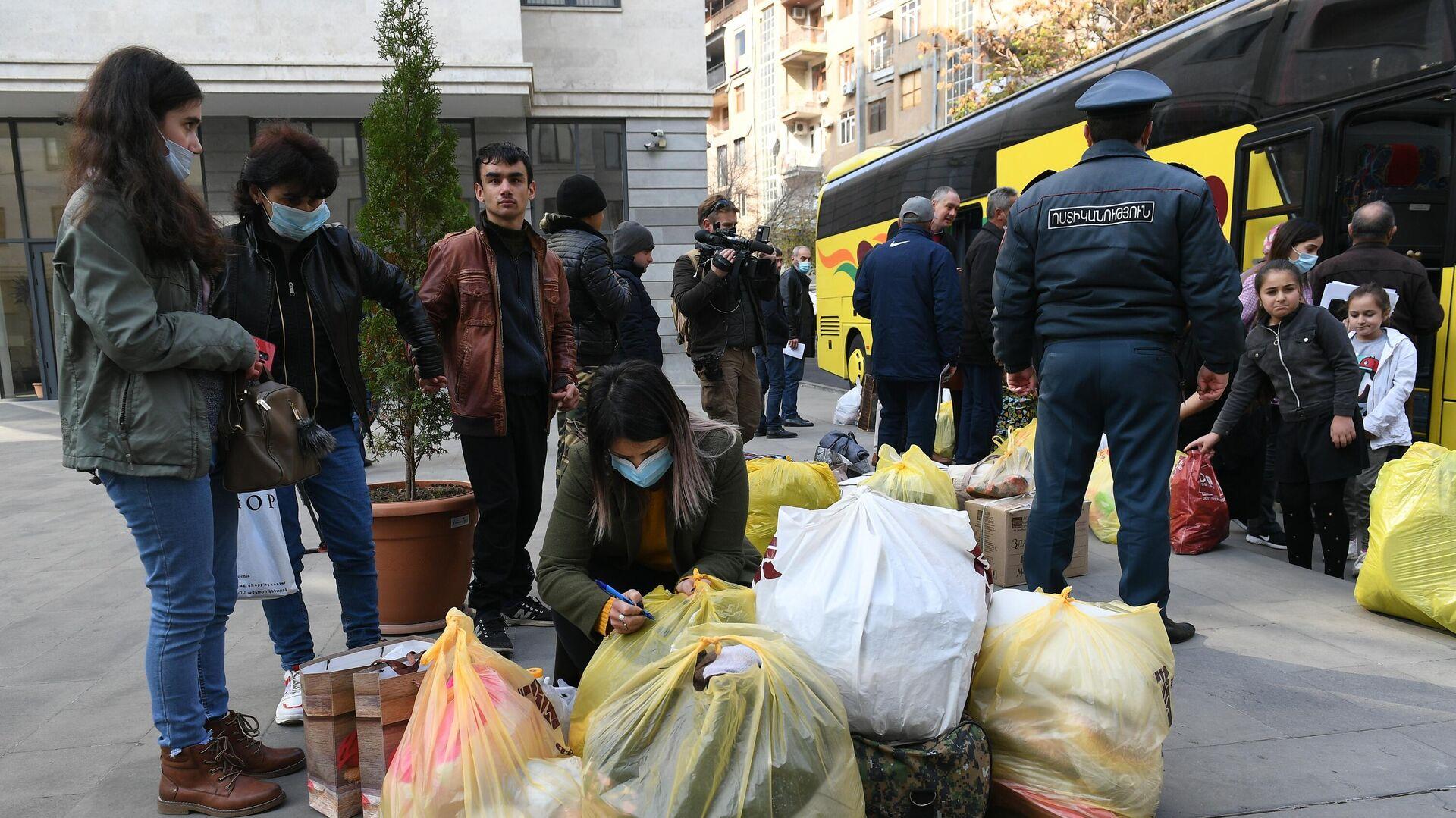 Беженцы из Нагорного Карабаха садятся в салон автобуса в Ереване во время возвращения домой в Степанакерт - РИА Новости, 1920, 01.12.2020