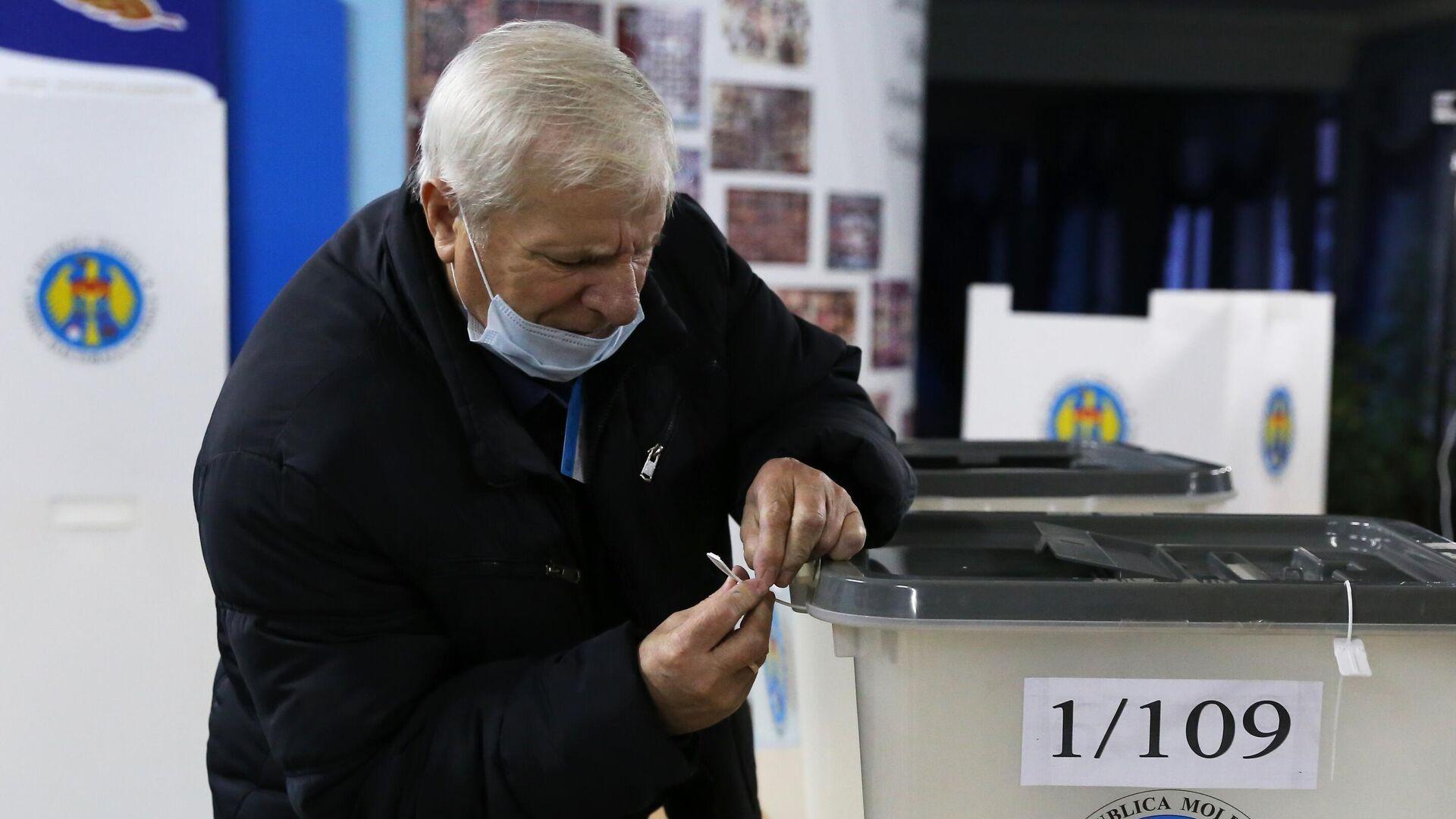 Член избирательной комиссии пломбирует избирательную урну на избирательном участке в Кишиневе - РИА Новости, 1920, 15.11.2020