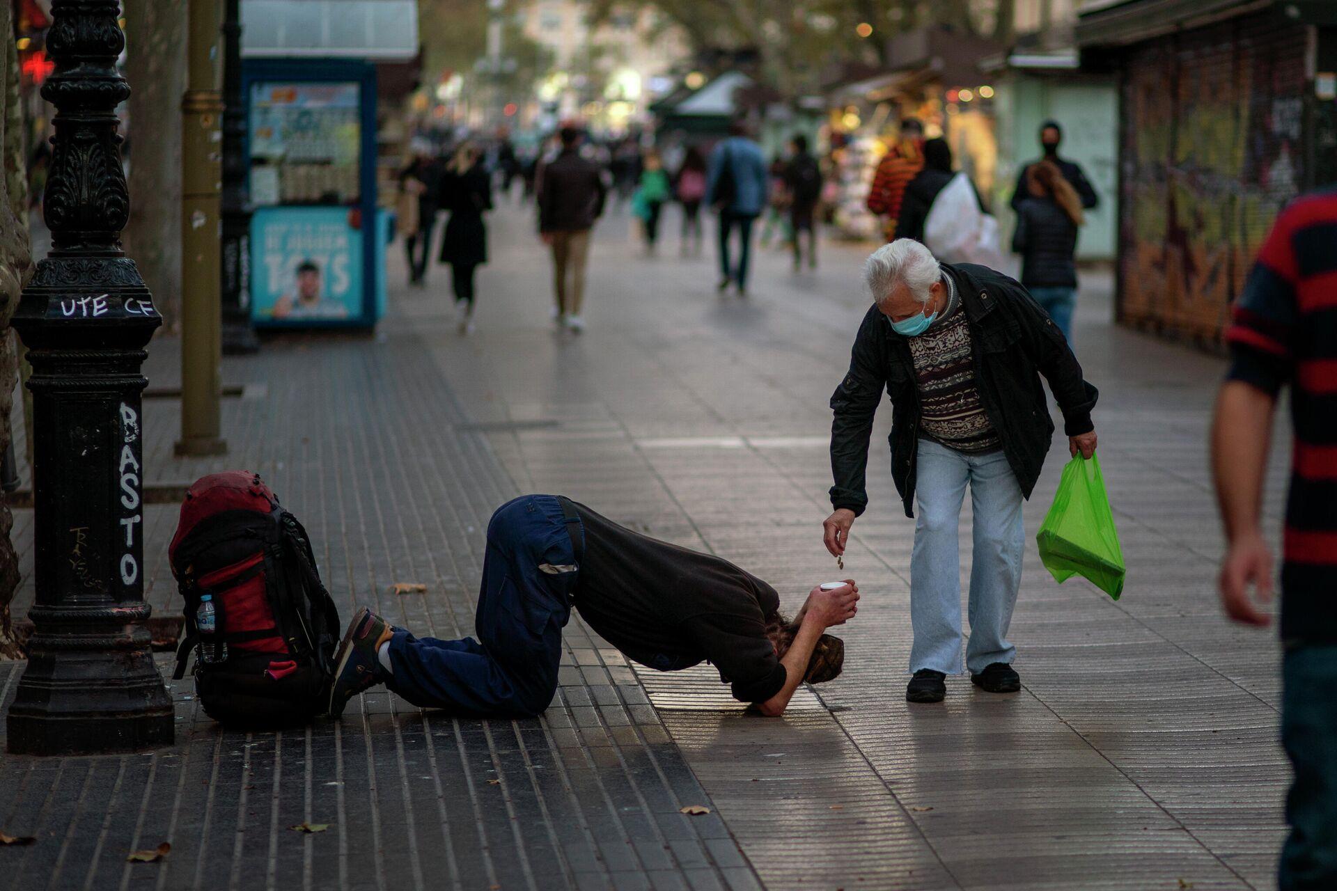 Мужчина подает милостыню нищему на бульваре Рамблас в Барселоне - РИА Новости, 1920, 17.11.2020