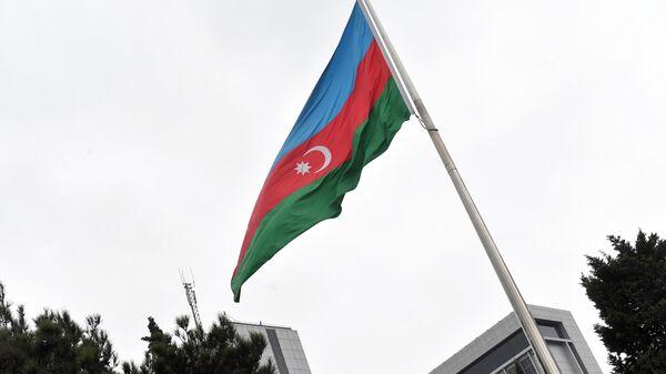 Государственный флаг Азербайджана на фоне здания Национального собрания Азербайджана в Баку