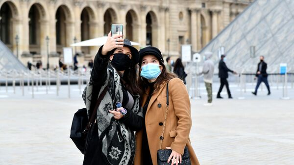 Девушки в масках фотографируются на площади у входа в музей Лувр в Париже
