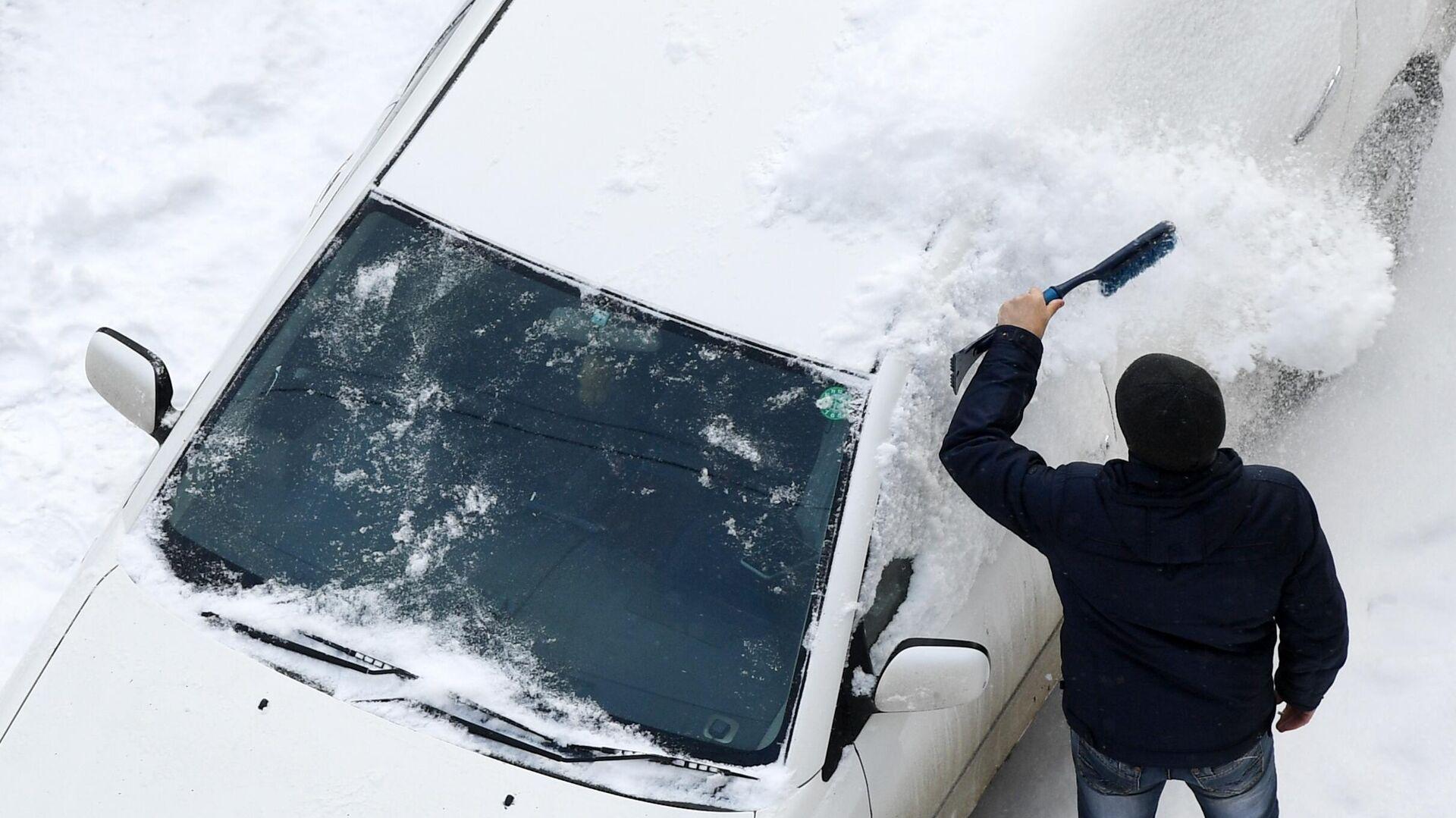 Мужчина сметает снег с машины - РИА Новости, 1920, 20.11.2020