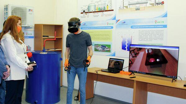 Специалист демонстрирует VR-игру для детей, где в школьном классе нужно найти возможности для энергосбережения, например, закрыть окно, кран или сменить лампочку накаливания на светодиодную