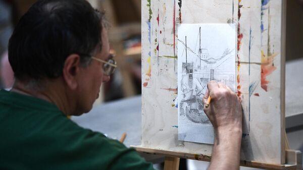 Мужчина рисует за мольбертом