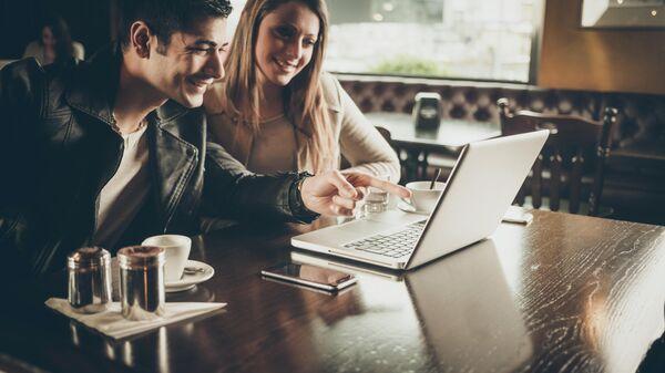 Молодые люди в кафе с ноутбуком