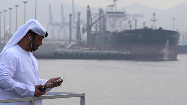 Местный житель на фоне нефтяного терминала в ОАЭ