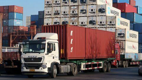 Грузовик с контейнером в логистическом центре недалеко от порта Тяньцзинь в Китае