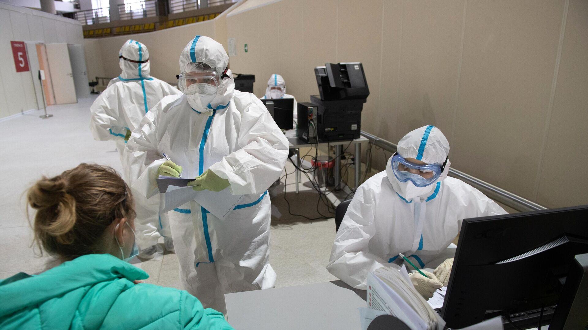 Медицинский работники приемного отделения осматривает пациентку во временном госпитале для пациентов с COVID-19, развернутом в ледовом дворце Крылатское - РИА Новости, 1920, 27.11.2020