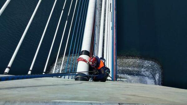 Спасатели-альпинисты Дальневосточного регионального отряда МЧС России во время очистки ото льда вант Русского моста во Владивостоке