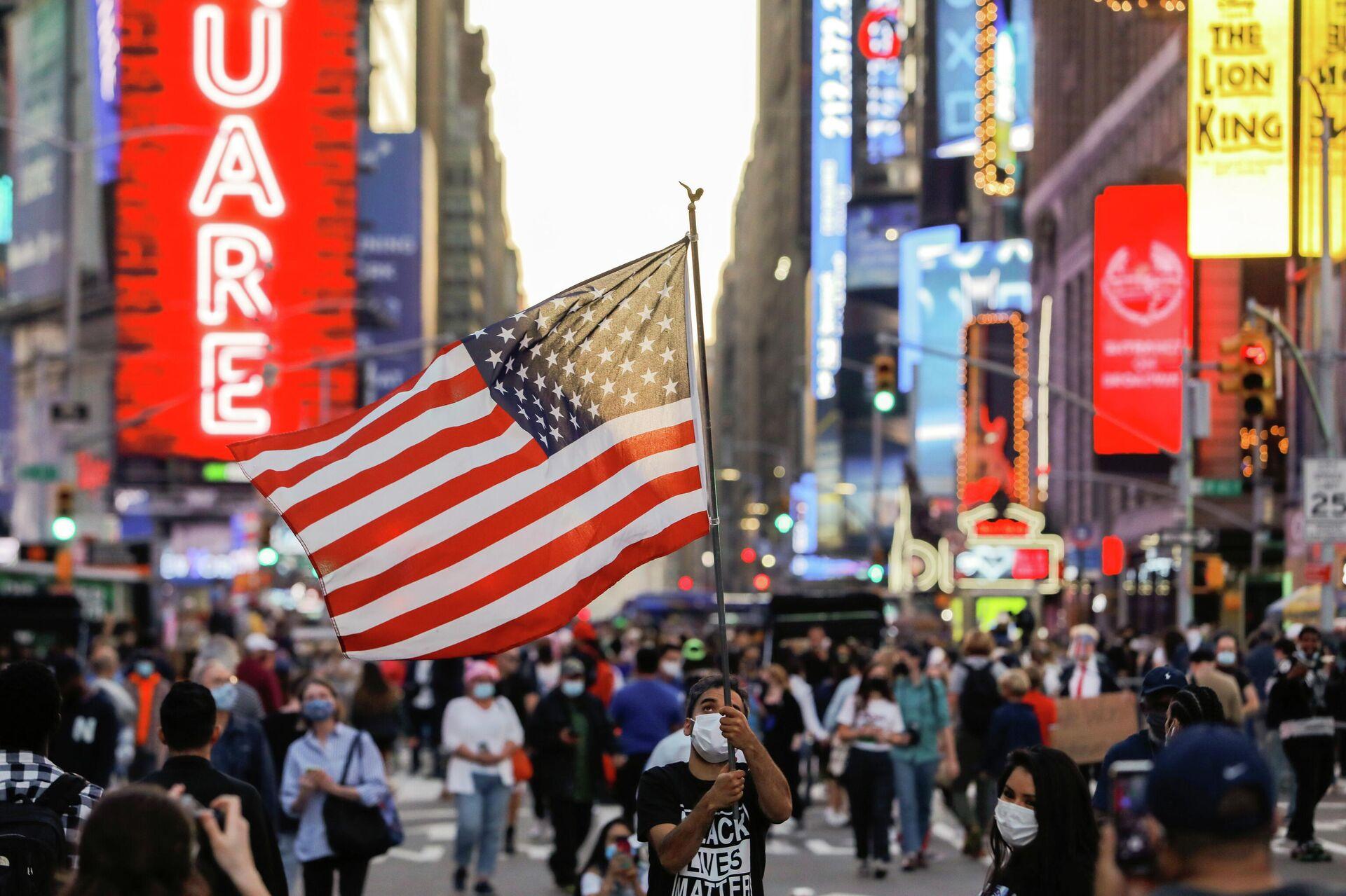 Мужчина с флагом США на Таймс-сквер в Нью-Йорке - РИА Новости, 1920, 14.12.2020