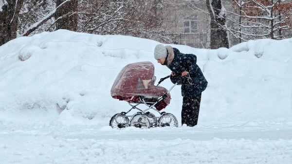 Женщина гуляет с коляской в парке