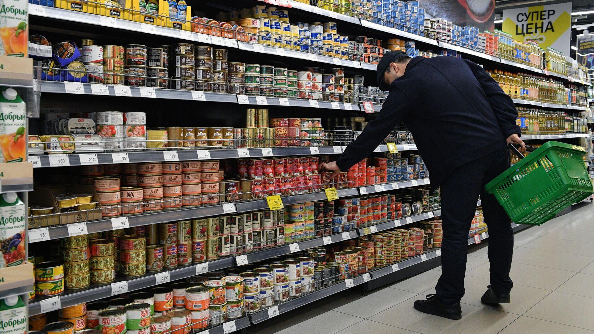 Покупатель выбирает консервы в одном из супермаркетов  - РИА Новости, 1920, 10.12.2020