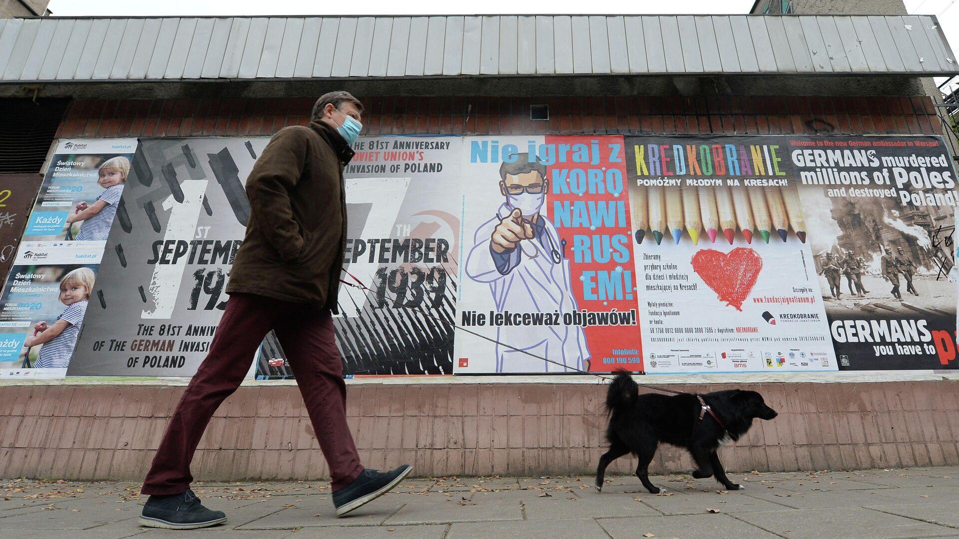 Мужчина с собакой проходит мимо плаката с предупреждением о том, что нельзя игнорировать симптомы COVID-19 в Варшаве - РИА Новости, 1920, 04.05.2021