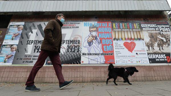 Мужчина с собакой проходит мимо плаката с предупреждением о том, что нельзя игнорировать симптомы COVID-19 в Варшаве
