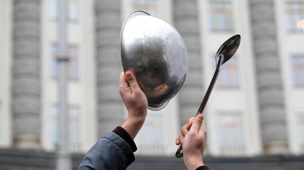 Участник митинга представителей ресторанного бизнеса против планов введения из-за пандемии коронавируса карантина выходного дня, который прошел у  здания кабинета министров Украины в Киеве