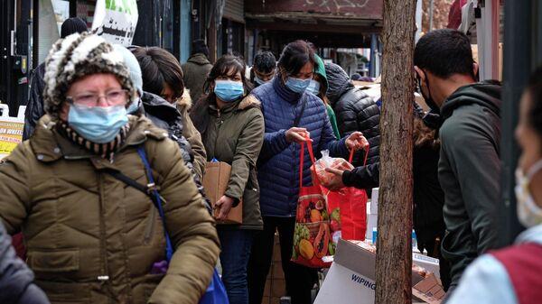 Сотрудник раздает продукты в пункте бесплатной раздачи еды в День благодарения в Бруклине