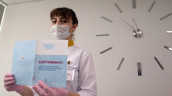 Медработник демонстрирует Сертификат о вакцинации от новой коронавирусной инфекции COVID-19