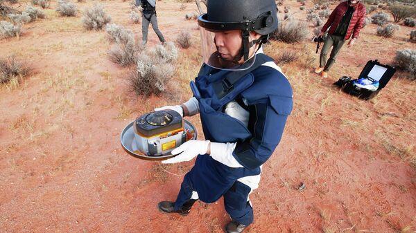Член команды JAXA с капсулой с грунтом, собранным космическим зондом Хаябуса-2 на астероиде Рюгу в Вумера, Австралия