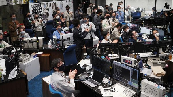 Участники проекта Хаябуса-2 наблюдают за прямой трансляцией возвращающейния капсулы в Сагамихаре, префектура Канагава