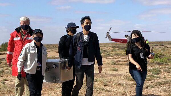 Сотрудники Японского агентства аэрокосмических исследований (JAXA) несут коробку с образцами астероида Рюгу, в районе Южной Австралии