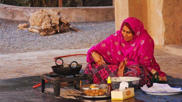 Женщина готовит еду в крепости Низва в Омане