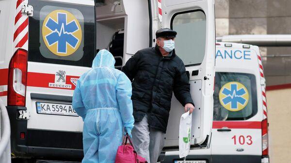 Медик и пациент у автомобиля скорой помощи в Киеве