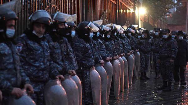 Сотрудники полиции следят за соблюдением порядка во время акции протеста около здания парламента Армении
