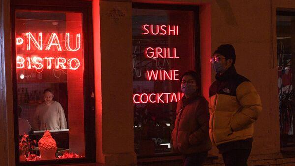 Прохожие идут мимо одного из кафе в Санкт-Петербурге