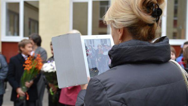 Женщина фотографирует учащихся средней общеобразовательной школы