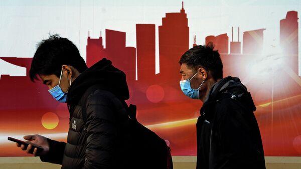 Люди в защитных масках на улице в Пекине, Китай