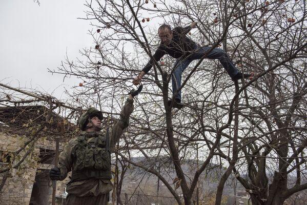 Местный житель угощает специалиста Международного противоминного центра Минобороны России гранатом вблизи Степанакерта в Нагорном Карабахе