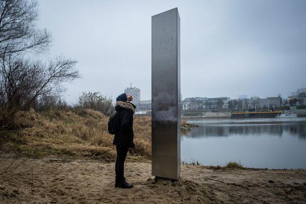 Девушка у металлической  стеллы на берегу Вислы в Варшаве