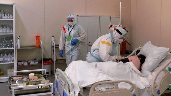 Медсестра кормит пациента в реанимационном блоке во временном госпитале для больных COVID-19, организованном в выставочном комплексе Ленэкспо